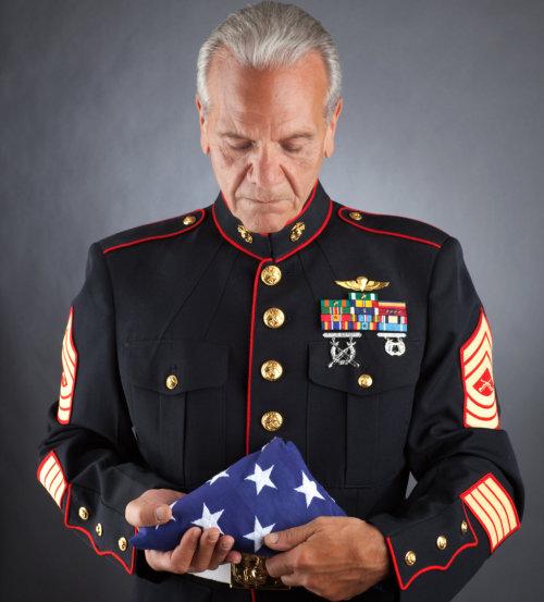 sad marine holding a flag