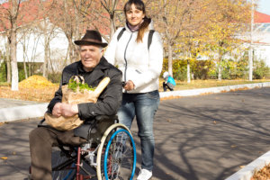disabled senior man having carrying a bread